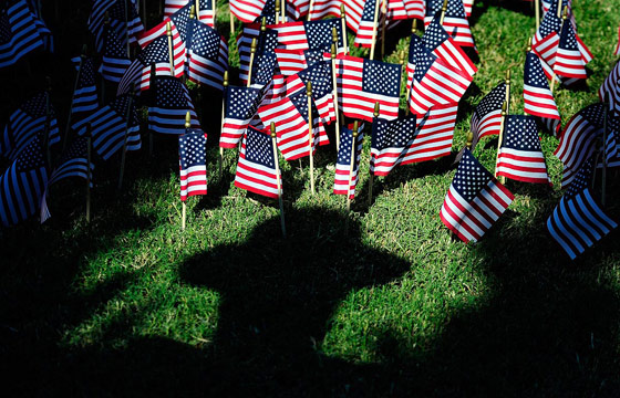 American flags, each representing firefighters lost during 9/11 and every year since, poke up from the ground near the shadow of an Augusta-Richmond Sheriff's Deputy during the 9/11 10th Anniversary Remembrance Ceremony at the Augusta Common in Augusta Sunday afternoon September 11, 2011.    Michael Holahan/Staff