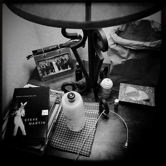 My bedside table in my old bedroom at my parents house consists of various books, water—drank out of my cycling water bottle—Kleenex, Chapstick, pain meds and an iPhone charger.