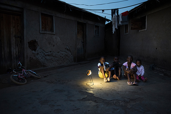 A group of children in Kisumu, Kenya sit in the courtyard between their houses in the neighborhood of Nyalenda B. They are lit by one solar lamp as the sun sets.