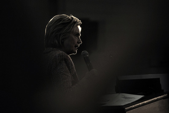 Hillary Clinton, silhouetted by a spotlight, speaks to supports inside a gym at Hartnell College in Salinas, Calif. on May 25, 2016.