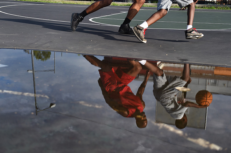 The reflection of DC native John Taylor, 52, left, and a neighborhood youngster is seen during a one-on-one basketball game at a Parkview neighborhood basketball court Tuesday, July 5, 206 in Washington D.C.  (Photo by Christian K. Lee/The Washington Post)