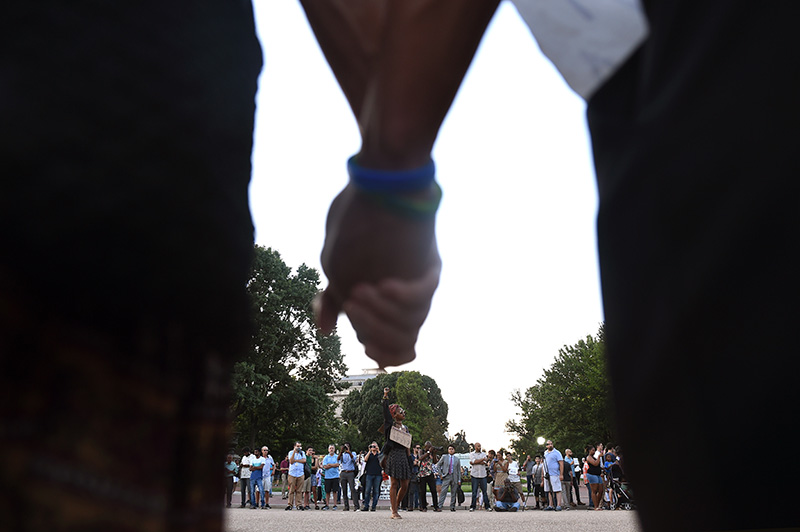 Arykah Bradford, 33, speaks to protestors as they joins hands during a demonstration in front of the White House on Friday, July 8, 2016 in Washington, DC. The demonstration was held in response to the officer involved shooting deaths' of Philando Castile and Alton Sterling. (Photo by Christian K. Lee/The Washington Post)