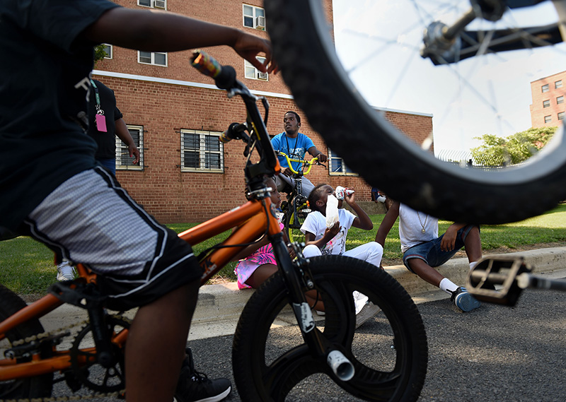 "Antonio Brown, 24, watches over children as they ride their bikes and hang out at the ""Beat the Streets"" community event Wednesday, June 29, 2016. The event is part of  DC's summer crime initiative to promote non-violence in communities. (Photo by Christian K. Lee/The Washington Post)"
