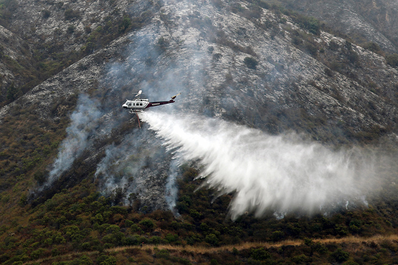 A helicopter drops water on Mt. Manuel in the Big Sur valley on August 11.