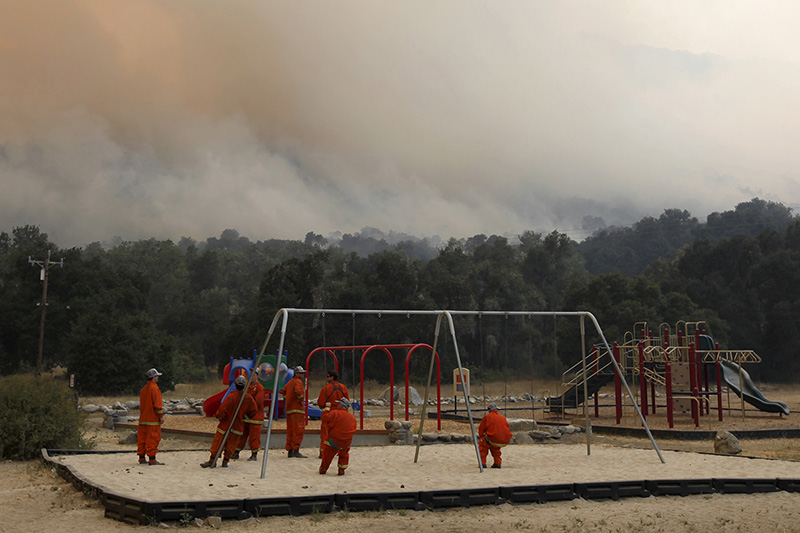 Inmate fire crews take a break at Cachagua Community Park while smoke from the Soberanes Fire fills the sky on August 6.