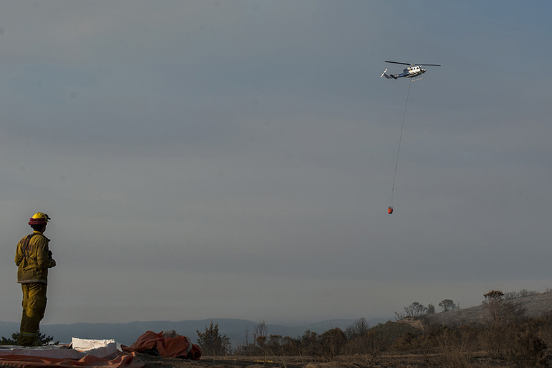 A firefighter watches a helicopter water drop over Palo Corona near Carmel Highlands on July 27.