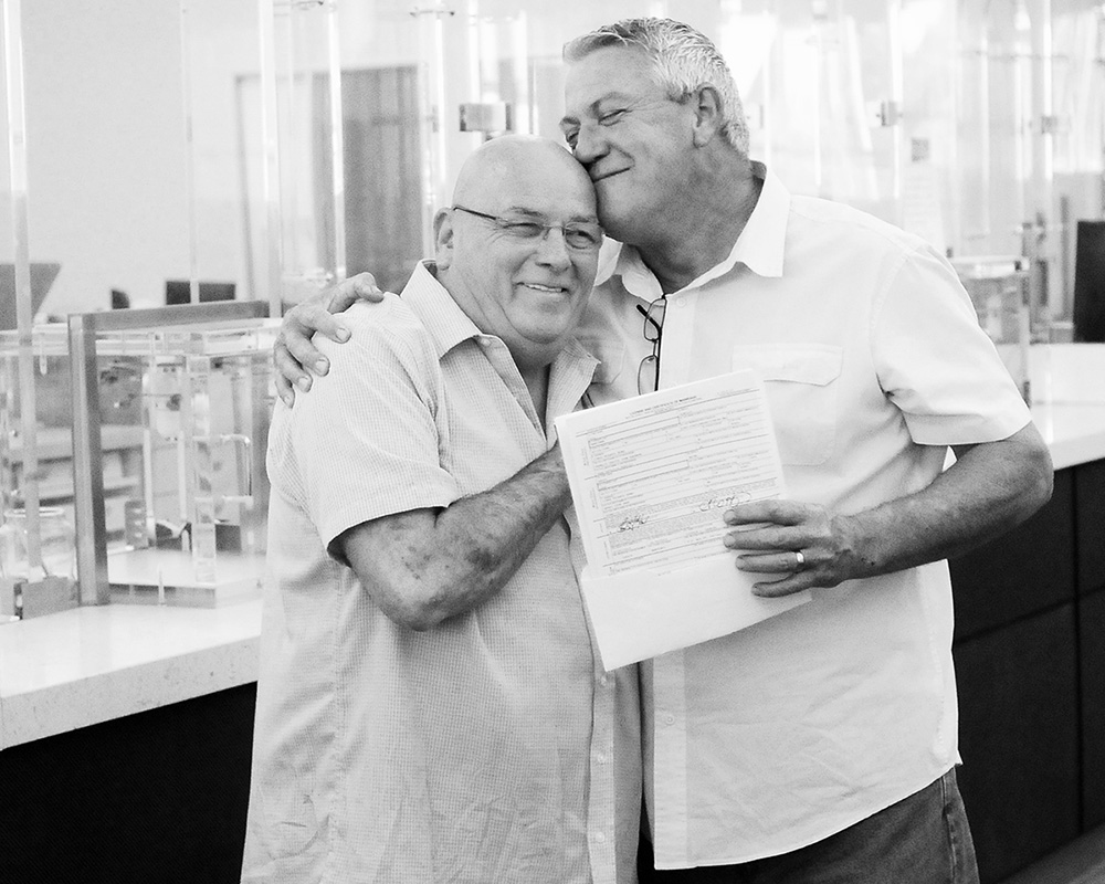 Grady Harp, right, hugs his husband Paul Hardiman shortly after the couple signed a marriage license at the Monterey County Government Building in Salinas, Calif. in July 2013. The couple was one of the first to get a marriage license after gay marriage was legalized in Monterey County.